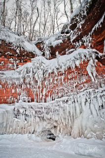 Ice formations hang over colorful rock face at Apostle Islands National Lakeshore in Northern Wisconsin.