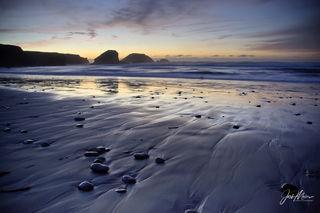 A soft twilight glow accents the purple sand of Pfeiffer Beach on California's Big Sur Coast.