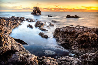 A long exposure smooths gentle waves and receding tide into a dreamlike sunset view of the sea at Little Corona Del Mar State Beach in Orange County, California