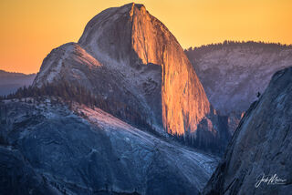 Sunset paints the iconic face of Half Dome in Yosemite National Park, California.
