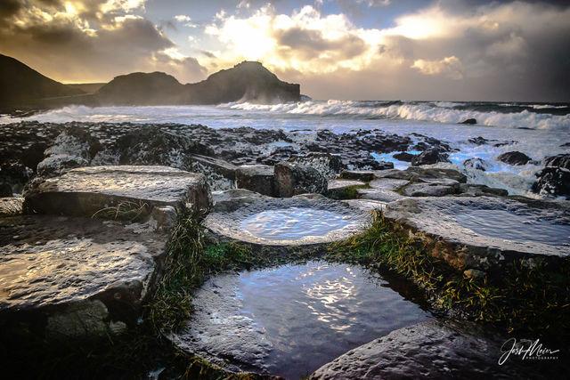 Waves crashing beneath stormy skies at Giant's Causeway along the Irish Sea in Northern Ireland.