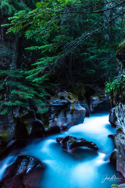 A long exposure image of water rushing through Avalanche Gorge at nightfall in Montana's Glacier National Park.