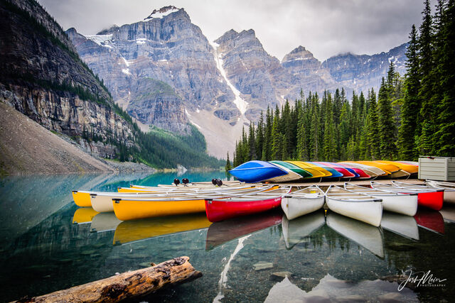 Dockside canoes add a splash of color to an overcast morning at Moraine Lake in Alberta's Banff National Park.