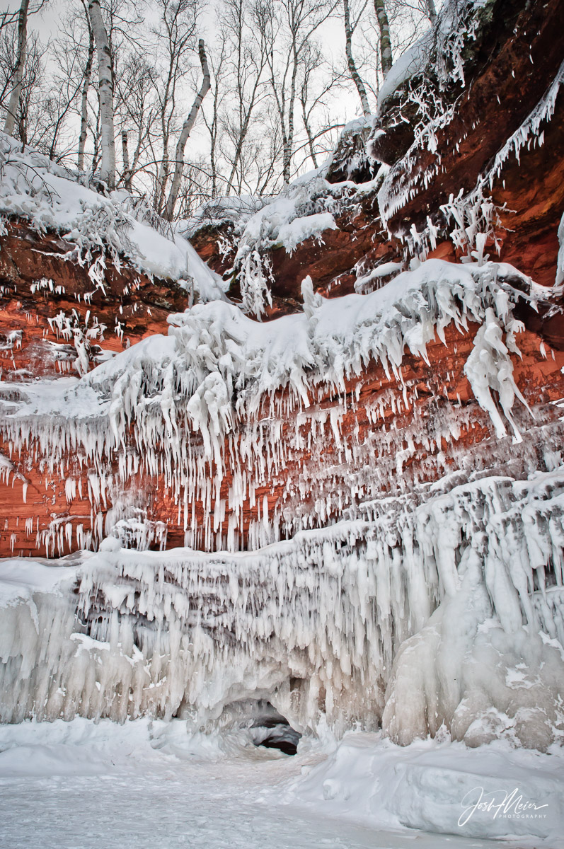 Ice formations hang over colorful rock face at Apostle Islands National Lakeshore in Northern Wisconsin. When conditions...