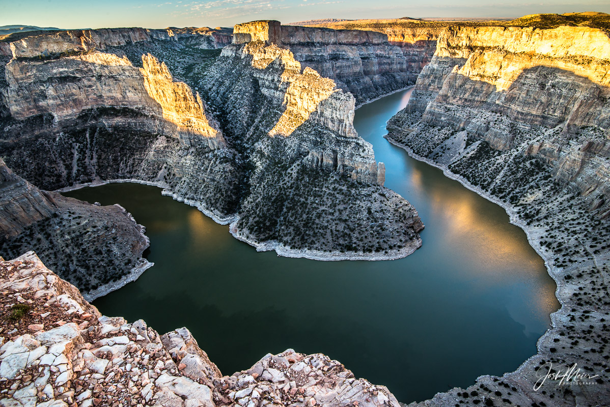 Glowing cliffs are reflected in a horseshoe bend of the Bighorn River as early morning light drops into the canyon depths.