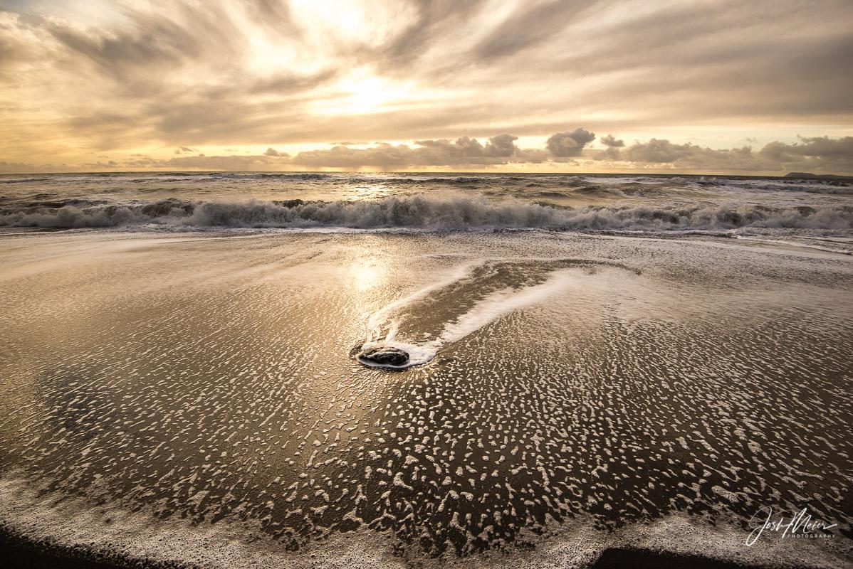 Receding waves reflect hues of a golden sunset along a remote beach at Point Reyes National Seashore, California.