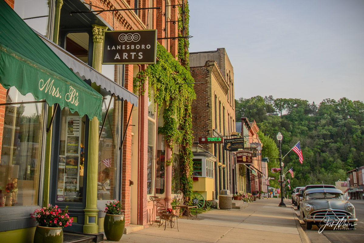 A classic car under the Stars and Stripes offers a slice of vintage Americana in this charming Main Street scene from the Lanesboro...