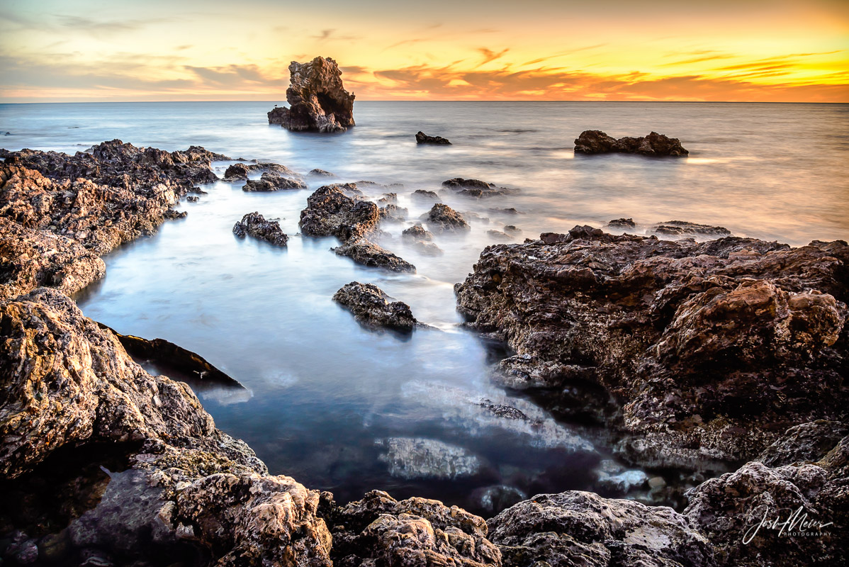 A long exposure smooths gentle waves and receding tide into a dreamlike sunset view of the sea at Little Corona Del Mar State...