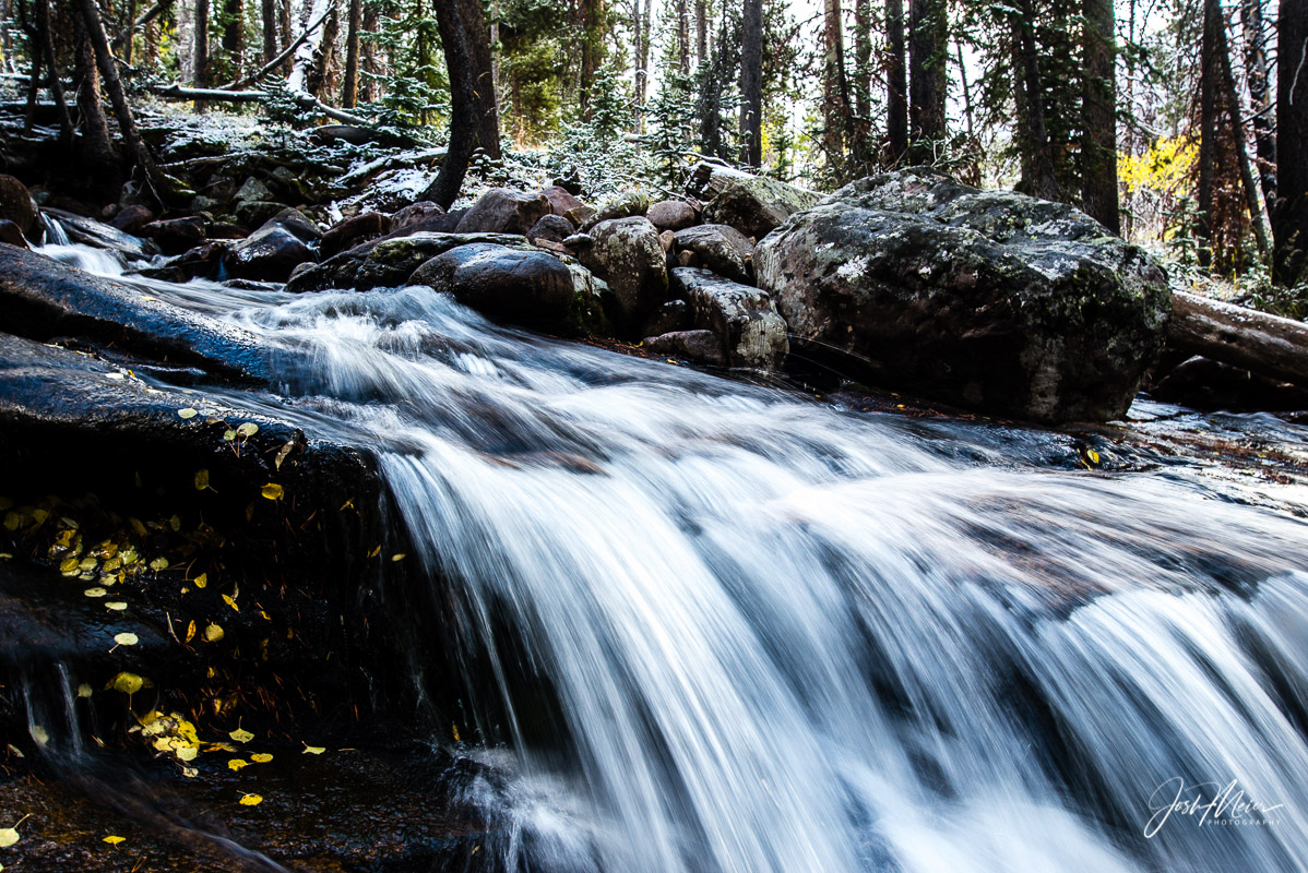 A cascading stream in the High Uintas Wilderness bordered by fallen leaves and traces of the year's first snow.