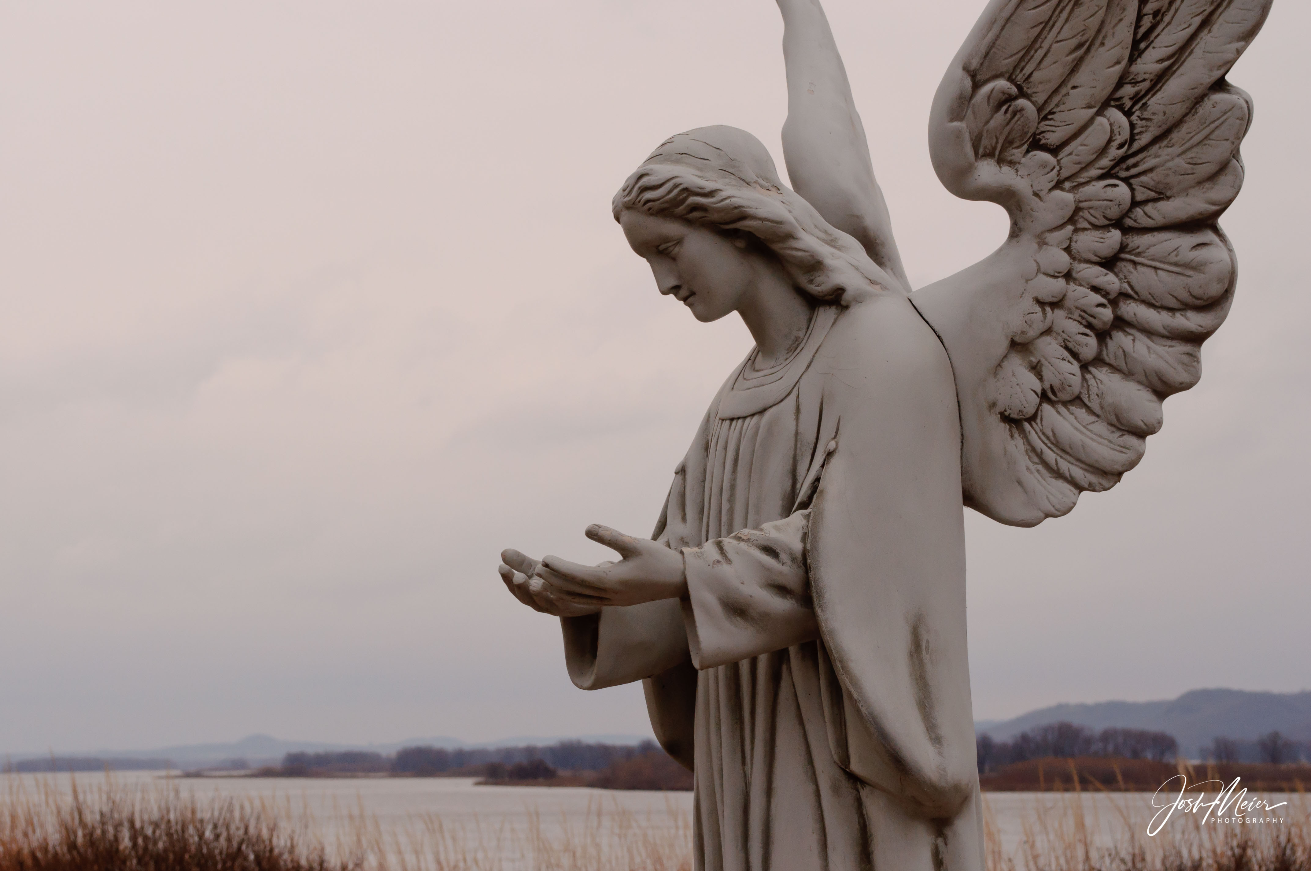 An angel statue looking westward from the banks of the Mississippi River in Bellevue, Iowa.