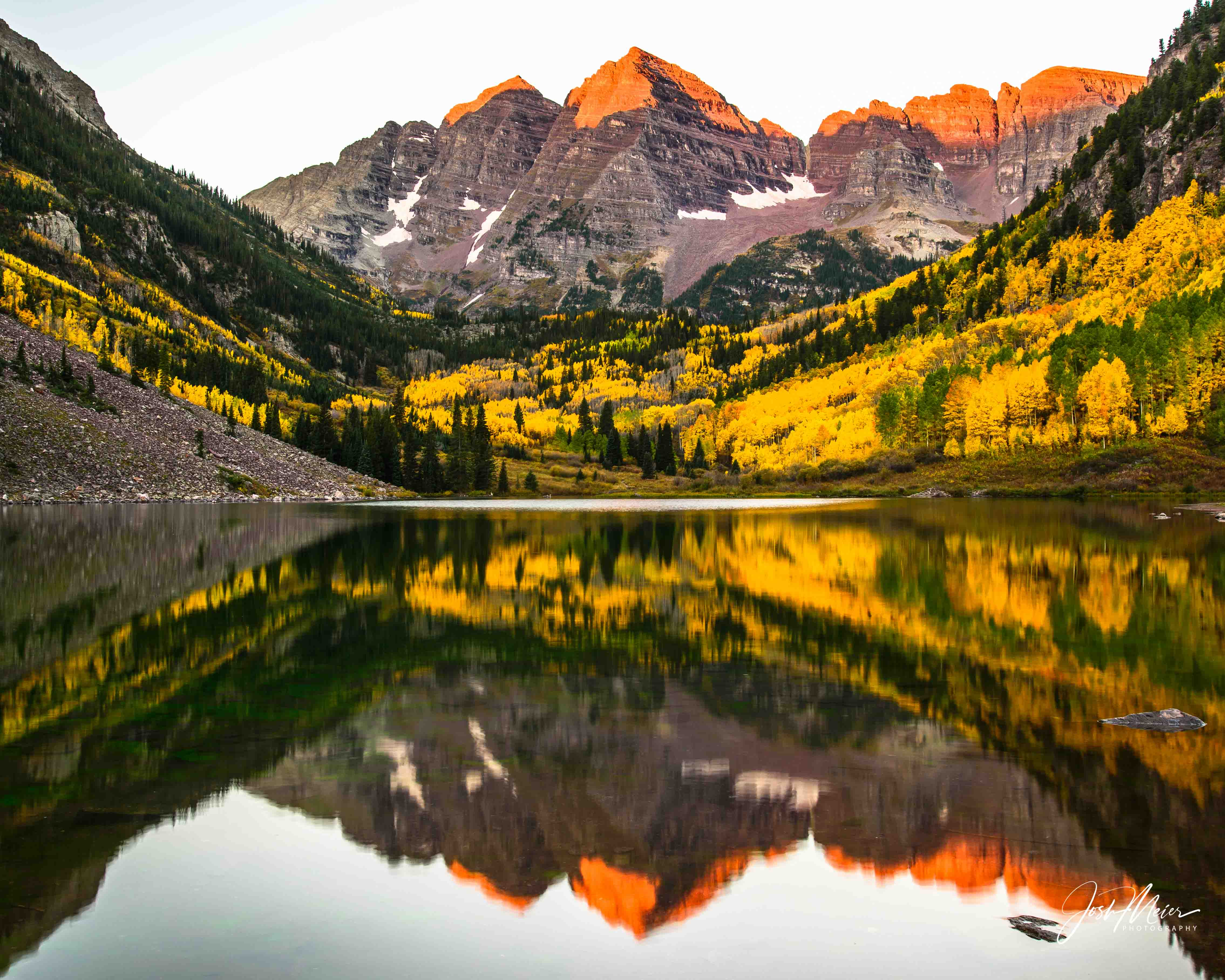 Sunrise alpenglow sets the peaks ablaze in this traditional lakeside view of the iconic Maroon Bells. Said to be the most photographed...